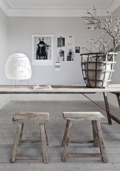 Stoere houten eettafel met bijpassende krukjes. Mooie lichtgrijze muur met zwart/wit fotos op achtergrond.