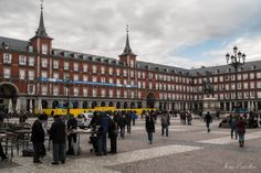 Plaza Mayor (Madrid) - The Plaza Mayor (English Main Square) was built during Philip III's reign (1598–1621) and is a central plaza in the city of Madrid, Spain. It is located only a few Spanish blocks away from another famous plaza, the Puerta del Sol. The Plaza Mayor is rectangular in shape, measuring 129 m × 94 m (423 ft × 308 ft), and is surrounded by three-story residential buildings having 237 balconies facing the Plaza. It has a total of nine entrance ways. The Casa de la Panadería…