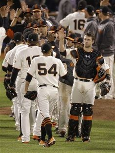 San Francisco Giants catcher Buster Posey, right, high-fives pitcher Sergio Romo (54) after Game 6 of baseball's National League championship series against the St. Louis Cardinals Sunday, Oct. 21, 2012, in San Francisco. The Giants won 6-1 to tie the series at 3-3.
