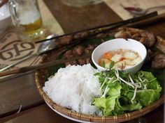 A plate of bun is served alongside a bowl of grilled pork patties, which after being grilled, are served in a smokey sour soup, and finally a plate of herbs and green vegetables are served to accompany everything