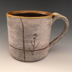 Hamada inspired mug made of local Virginia Clay covered with porcelain slip carved tenmoku liner glaze wood fired in our three chamber noborigama.  by citybytheseaceramics