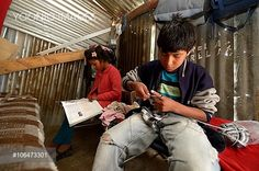 Adolescent boy, 14 years, knitting a scarf, his sister, 12 years, doing her homework, in a simple hut made of corrugated iron, Ayacucho, Ayacucho region, Peru