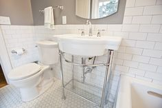 """The second floor 1920's bath was ready for a remodel. With a cracked floor and inadequate subfloor, the bathroom rug was no longer a good """"fix"""". Keeping the age of the home in mind, white subway tile and a hexagon floor tile were installed. Beautiful fixtures were selected including a new American Standard sink console. …"""