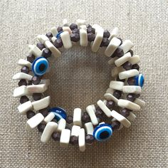 THE CLARAVAL BRACELET – This is an easy to wear bracelet with no clasp, made with bones, brown beads and blue evil eye, it just needs to wrapped around the wrist and is perfect for everyday or special occasions.  Artistic detail added by greek/turkey – blue evil eye amulet. Evil eye jewelry gives happiness to the friends and the beloved ones. Protection from the evil eyes, covetous friends and strangers.
