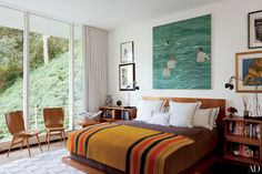 The '20s Pierre Chareau pearwood bed in one of the bedrooms of decorator Waldo Fernandez's Los Angeles home has an integrated side table and bookshelves and is dressed with an Hermès blanket; the large painting is by Hernan Bas, and the chairs are by Oscar Niemeyer | archdigest.com