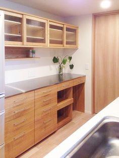 チェックガラスを使用したタモ材のキッチンの壁面収納。 吊り棚+カップボードのタイプは使いやすく、人気のオーダー…