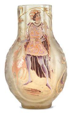 Émile GALLÉ (1846-1904)  Vase de forme bombée à col droit polylobé en verre légèrement givré à décor émaillé polychrome de personnage du Moyen Age avec son lévrier sur fond de rameaux fleuris. Signé. H.: 24 cm. Bibliographie: - Modèle similaire répertorié page 157 dans Carved and decorated art glass par Ray et Lee Grover, Charles Tuttle 1970.
