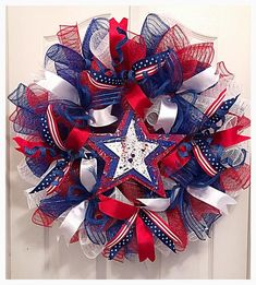 Celebrate Patriotic Holidays, Labor Day or a Solders Homecoming with this red, white and blue deco mesh wreath. It is made with Flag ribbons, silky ribbons and glittered springs. The center of the wreath is made with a three layered wooded star that shows Wreath Crafts, Diy Wreath, Wreath Ideas, Wreath Bows, Flower Wreaths, Patriotic Wreath, 4th Of July Wreath, Patriotic Crafts, American Flag Wreath