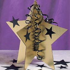 The Gold 3D Star Centerpiece features a 3D gold star with smaller black star accents and curling ribbon. Each set of six Gold 3D Star Centerpiece are made of cardboard.