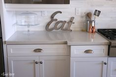 Caesarstone London Grey Quartz countertops in a white and gray kitchen. Glass cake stand and top on display.