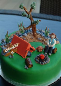 Camping cake - gumpaste tent, sleeping bag, wooden sign, campfire, tree, stream and boy roasting a marshmallow
