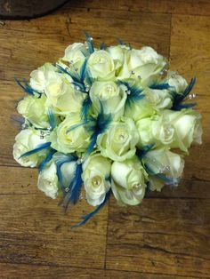 Avalanche roses with gem centres and teal feathers , presented as a hand tied.