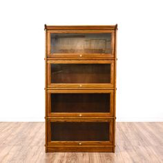 This lawyer's bookcase is featured in a solid wood with a glossy oak finish. This American traditional style bookshelf has glass front doors, 4 rows of shelving, and simple straight sides Perfect for the home office! #americantraditional #storage #bookcase&shelving #sandiegovintage #vintagefurniture
