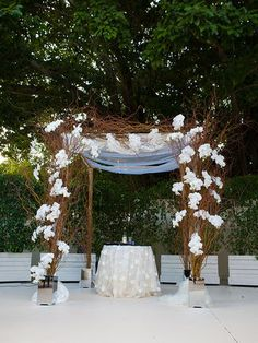 A natural orchid and willow branch decorated chuppah for an outdoor wedding