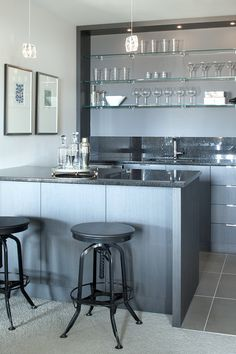 Contemporary wet bar with steel gray cabinets paired with speckled black countertops and black granite backsplash.