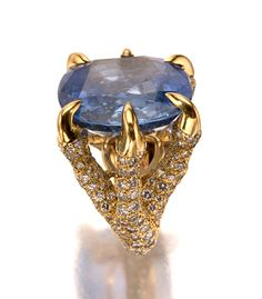 SAPPHIRE AND DIAMOND RING, MONTURE CARTIER.  The mount pavé-set with brilliant-cut diamonds designed as a pair of bird claws clutching a cushion-shaped sapphire, mounted in yellow gold,  inscribed Monture Cartier.  size 47, sizing band,