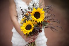 a bouquet with sunflowers and local sage and grasses. She wanted the bouquet to be free and funky. The actually went out a few days before the wedding and picked sage, which grows like a weed in central oregon. We also put chrysanthemums, carthamus and wheat in the bouquets.!