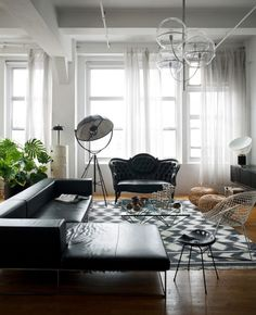 salon de style masculin avec un canapé en cuir gris, fauteuil classique gris, tapis en noir et blanc à motifs géométriques