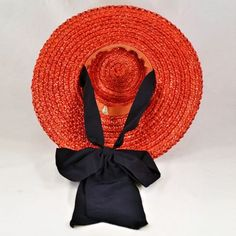 Cherry-red straw hat with blue ribbon (inside view) | Small, flat crown and a great wide brim which gives the hat a touch of class with the added benefit of sun-blocking protection | The big, bold bow at the bottom is permanently knotted but features two small bands of elastic so it can be slipped comfortably under the chin