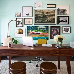 The aqua wall in this home office provides a playful backdrop for an irreverent art collection.
