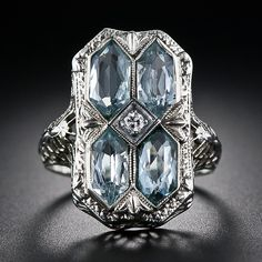A 1920's aquamarine Art Deco filigree ring in 14 karat white gold. Four pale hexagonal cut aquamarines are set across the top and centred with a small transitional round brilliant cut diamond.