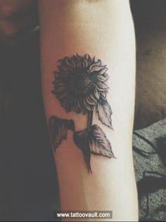 Black sunflower tattoo on arm