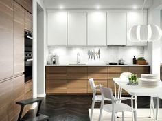 Cuisine avec portes effet noyer, portes blanches et plan de travail blanc. Une hotte en acier inoxydable, un four et un four à micro-ondes gris foncé complètent l'ensemble.