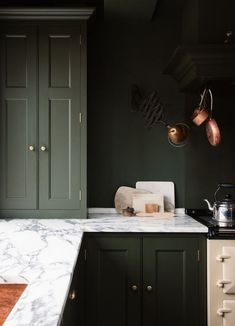 Copper pans stand out against dark green kitchen walls and kitchen cabinets See why green kitchen cabinets are having a moment right now. Browse stunning spaces that utilize the hue and get paint ideas for your own kitchen. Green Kitchen Walls, Dark Green Kitchen, Green Kitchen Cabinets, Kitchen Wall Colors, Farmhouse Kitchen Cabinets, Kitchen Tops, Painting Kitchen Cabinets, Kitchen Paint, Dark Cabinets