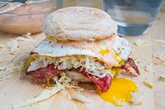 Breakfast Reuben Sandwich -- 1 english muffin (preferably rye), lightly toasted 2 slices corned beef, warm 2 tablespoons swiss, shredded 2 tablespoons sauerkraut, squeezed and drained, coarsely chopped 1/8 teaspoon caraway seeds, toasted and ground 1 tablespoon russian or thousand island dressing 1 egg, fried