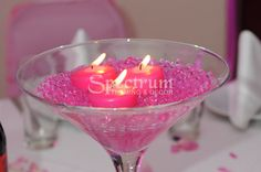 Pink martini glass with floating candles and gel.