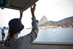 Woman lifting campervan door, Rio de Janeiro, Brazil