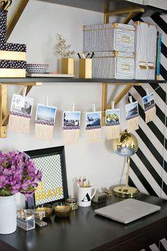 Vista de un escritorio negro con repisas negras y soportes dorados, Cajas y porta lápices dorados o con detalles dorados. Sobre el escritorio culegan de un cordel fotografías afirmadas con perritos de ropa. En el escritorio una lámpara dorada, accesorios de escritorio y un florero blanco con flores.