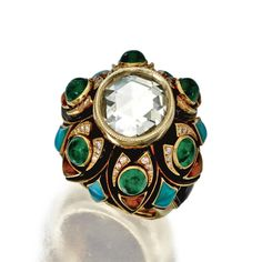 DIAMOND AND COLORED STONE RING, BULGARI, FRANCE, CIRCA 1970 The rose-cut diamond measuring approximately 11.7 by 11.5 mm., framed by small round diamonds weighing approximately .25 carat, variously-cut cabochon emeralds, citrines and turquoise, and onyx tablets, mounted in 18 karat gold, signed Bulgari, French workshop mark, French assay mark.