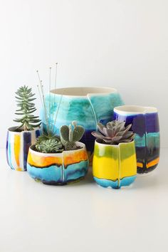 oh dear. I am completely smitten with these colorful earthenware vessels. as if the succulents weren't cute enough!