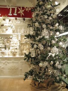 Stunning Ivory-Platinum themed Christmas tree from the Bethany Lowe Designs showroom. This tree is adorned with ornaments, paper houses, and glittered netting. http://bethanylowe.com/