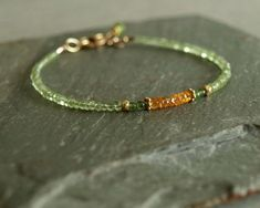 Small fine natural green peridot and green jade surround vibrant Mandarin orange garnet with small gold beads in this tiny bead bracelet. It