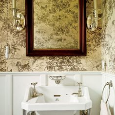 Little powder room on the island of Nanucket in Massachusetts. Sconces, wooden mirror frame, paneling and I love this wall paper. I wonder what the name of the paper is?