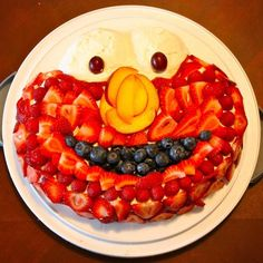 """My kids and I love this recipe of elmo"""" prepared with fruits! first formed a delicious cream for cakes in circle form, then with strawberries cut some,and not others  we are the top of the cream, leaving free space for your mouth which also sits on top of the cream but with grapes, and the space of the nose also make it free to make with pieces cut of apples, then take a spoon to fill us serve the rich ice cream vanilla,and take ice cream and put two tablespoons for resemble Elmo's eyes…"""