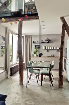 Un comedor en grises y con columnas de madera. ¡Menuda envidia!