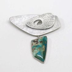 This one of a kind Mid-Century Modern inspired brooch has floating layers of textured sterling silver separated by silver tubes and connected with hand forged rivets. A rustic stone of Peruvian Blue O