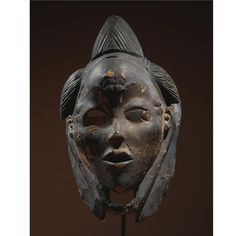 A MAGNIFICENT PUNU-LUMBO MASK, GABON of overall graceful proportions and hollowed, oval form, with pointed chin, tender sensually parted lips, petite nose flanked by pronounced cheekbones, beneath squinting eyes and dramatically arching brows, framed by diminutive ears, with notched scarifications on the bulging forehead and temples, the whole surmounted by an upswept crested coiffure flanked by chignons with rests of fibres at each end for attachment of braids