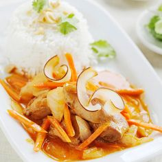 Coconut-Curry Chicken  Coconut curls and fresh cilantro top this spicy chicken dish, served with a side of steamed white rice.