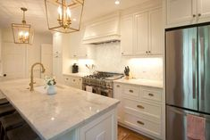 Custom white cabinets with antique brass fixtures and hardware.  Stainless steel appliances seem to not clash with the brass!