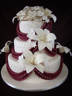 Torta de 3 gradas cubierto de pasta de azúcar de marfil y cubierto con flores de azúcar y burdeos drapeado rojo: