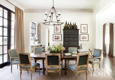 In this Buckhead dining room, a set of chairs upholstered in Great Plains fabric sidle up to a stately oval dining table by Dennis & Leen.