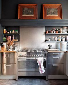 wow kitchen. Stainless steel range and base cabinets with dark gray hood above them, two framed pictures above the stove balance things.
