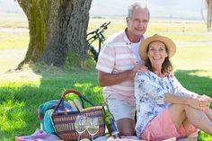 Starszy para siedzi na kocu piknikowym