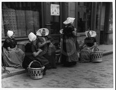 Mid-20th century, Netherlands --- Traditionally dressed women sit knitting at the side of a street. --- Image by ? Hulton-Deutsch Collection/CORBIS