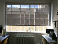 Sunscreen roller blind for large window in warehouse apartment | Fitted outside the recess and reverse roll to allow for inward opening windows | Allows a view out and stops glare whilst providing shade | Made to measure | Dalston, East London