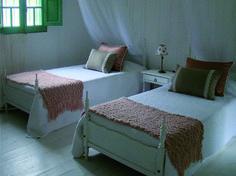 Decoración dormitorio romántico en una campo. Mucho blanco, mantas en pie de cama tejidas, almohadones en lino con puntillas y en pana con madroño. Estudio Prágmata